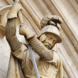 Stock Photo: Medieval knight killing a dragon from gothic facade of public historical building on Grand Place in Brussels
