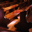 Pink and violet reflections from stained glass windows in church on benches — Stock Photo #12286681
