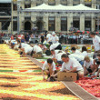 Stock Photo: Unidentified volunteers of different ages arrange flowers for Flower Carpet