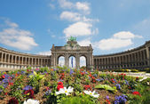 Triumphal Arch in Cinquantennaire Park in Brussels in summer with flowers on front of it — Stock Photo