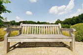 Big bench in garden in bright summer day — Stock Photo