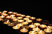 Small firing candles in catholic church on dark background — Stock Photo