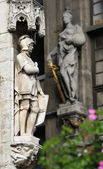 Realistic gothic statues decorating facades of Grand Place in Brussels and blurred flowers — Stock Photo