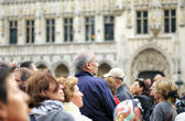 Foreign tourists listen to guide on crowded in season Grand Place on June 16, 2012 in Brussels — Stock Photo
