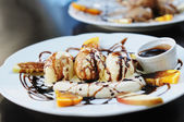 Scoops of coffee ice-cream with chocolate syrup and orange on white plate — Stock Photo