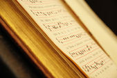 Shallow DOF image of antique church book for prayer with old style musical signs — Stock Photo