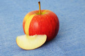 Red apple Pirouette with cut slice on blue — Stock Photo