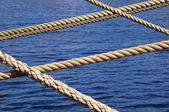 Ropes on sail boat and blue water — Stock Photo