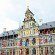 Medieval building of City Hall in Antwerp decorated with flags of different countries in rainy day - Stock Photo