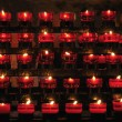 Rows of firing candles in catholic church - Stock Photo