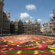 BRUSSELS, BELGIUM-AUGUST 15: Tourists from the entire world admire african theme Flower Carpet on Grand Place on August 15, 2012 in Brussels. This is biennial event with different themes. - Stock Photo