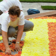 Stock Photo: BRUSSELS, BELGIUM-AUGUST 14: Unknown volunteer prepares Flower Carpet 2012 on August 14, 2012 in Brussels. This biennial event attracts thousands of tourists fro