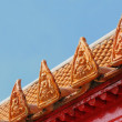 Fragment of roof of Buddhist temple in Thailand with ceramic tiles on blue sky — Stock Photo