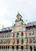 Medieval building of City Hall in Antwerp decorated with flags of different countries in rainy day — Foto de Stock