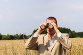 Police investigator watching through binoculars in the field — Stock Photo