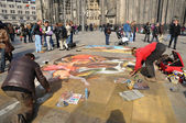 Street artists make a beautiful painting on a pavement on front of the cathedral — Stock Photo