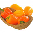 Yellow and orange peppers in a basket isolated on white — Stock Photo