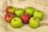 Red and green apples on a beige structured village table cloth — Stock Photo