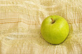 Green apple on a beige table cloth — Stock Photo