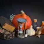 Magic books in vintage basket, hourglass, halloween pumpki — Stock Photo #32480313