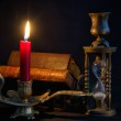 Vintage candlestick with red candle, books and hourglass — Stock Photo #32480325