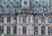 Building visible through glass covered by rain drops — Stock Photo