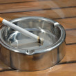 Metal ashtray with a cigarette on a wooden table — Stock Photo #51565725