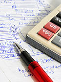 Red ball pen, calculator and sample text — Stock Photo