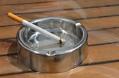 Metal ashtray with a cigarette on a wooden table — Fotografia Stock