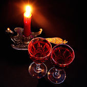 Red candle in vintage candlestick and two wineglasses of red wine — Stock Photo