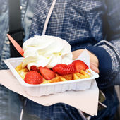 Hand of a tourist holding traditional Brussels delight gaufre — Stock Photo