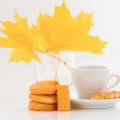 Coffee cup with cookies and yellow leaves — Stock Photo