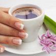 Beautiful manicured hand with french nails and cup of coffee and flowers at saucer — Stock Photo