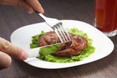 Cutting grilled steak with knife on white plate — Stock Photo