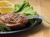 Grilled steak with salad and lemon on black plate with fork — Stock Photo
