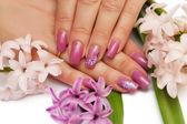 Woman hands with manicured nails and flowers — Stock Photo