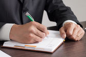 Businessman makes notes to his diary — Stock Photo
