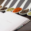 Opened Kitchen book with various of Spices — Stock Photo #26900823