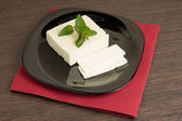 Sliced cheese on black dish with napkin — Stock Photo