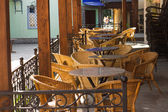 Street cafe with wicker chairs in morning — Stock Photo