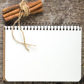 Blank Recipe book with bunch of cinnamon on old wood board — Stock Photo
