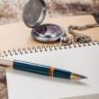 Golden in pen with pocket watch at white notebook — Stock Photo #31422325