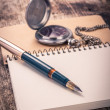 Vintage ink pen and pocket watch on notebook — Stockfoto