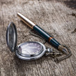 Old pocket watch and fountain ink pen on wood background — Stok fotoğraf