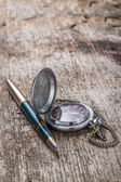Antique watch and ink pen on wood weathered background — Stock Photo