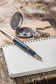 Golden in pen with pocket watch at white notebook — Stock Photo