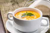 Pumpkin soup with green basil — Stock Photo