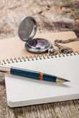 Złoty w pióro z zegarek kieszonkowy w białym notebooków — Zdjęcie stockowe