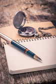 Vintage ink pen and pocket watch on notebook — Stock Photo