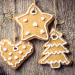 Gingerbread cookies hanging over wooden background. Christmas decoration — Photo
